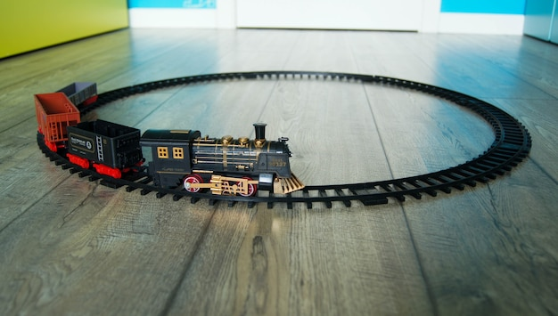Closeup of a retro toy train on the circular track on the floor of colorful kids room