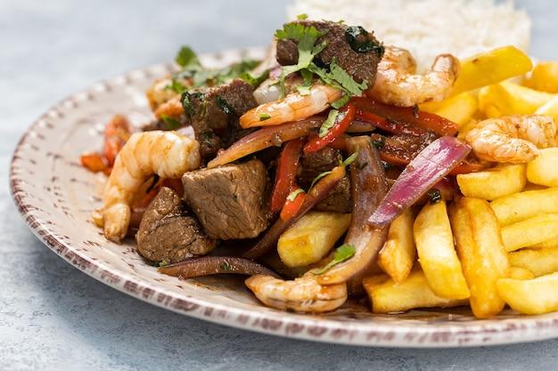 Primo piano di carne arrosto con salsa, verdure e patatine fritte in un piatto sul tavolo