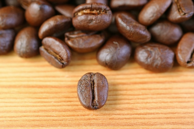 Closeup a robusta roasted coffee bean with blurry coffee beans pile in the backdrop