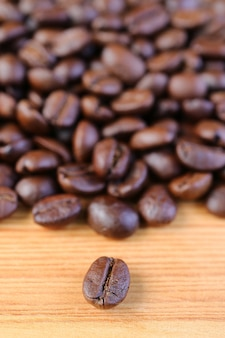 Closeup of a robusta roasted coffee bean with blurry coffee beans pile in background