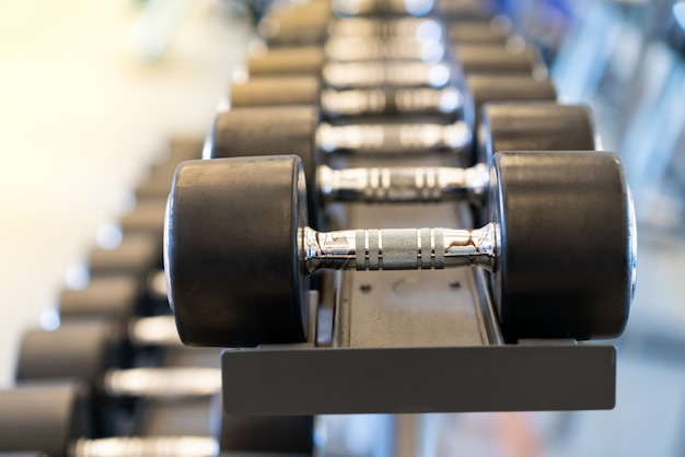 Closeup rows of metal dumbbells on rack in the gym