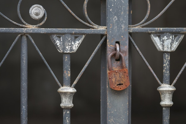Closeup of a rusty padlock on an old metallic fence in a graveyard