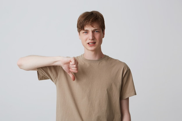Closeup of sad disappointed young man in beige t shirt