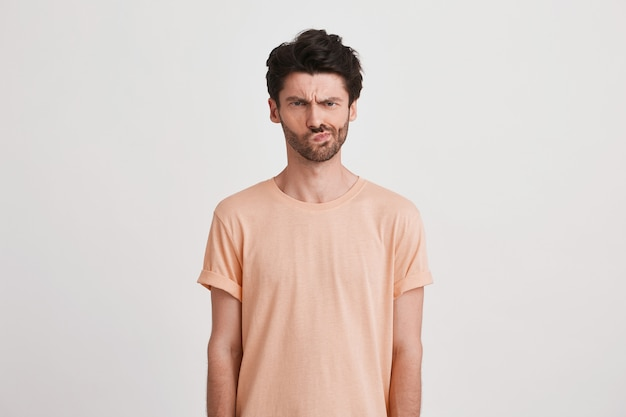 Closeup of sad dissatisfied young man with bristle wears peach t shirt feels displeased and frowning his face isolated on white