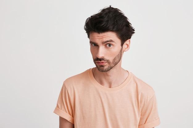 Primo piano del giovane triste insoddisfatto con setola indossa maglietta color pesca si sente dispiaciuto e aggrottando la fronte il suo volto isolato su bianco