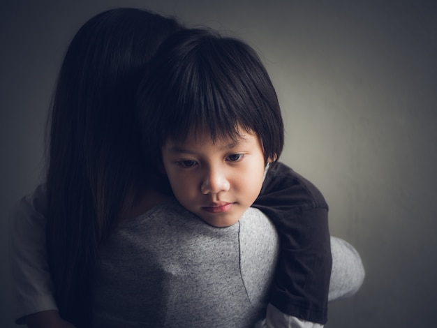 Closeup sad little boy being hugged by his mother at home