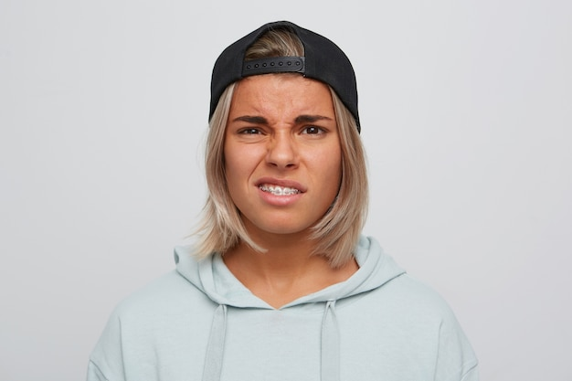 Closeup of sad unhappy blonde young woman with braces on teeth wears black cap and hoodie looks upset and displeased isolated over white wall