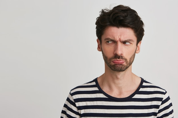 Closeup of sad upset bearded young man wears striped t shirt feels depressed, pressed lips and looks to the side isolated on white