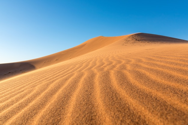 Primo piano delle increspature della sabbia sulle dune di sabbia in un deserto contro il chiaro cielo blu