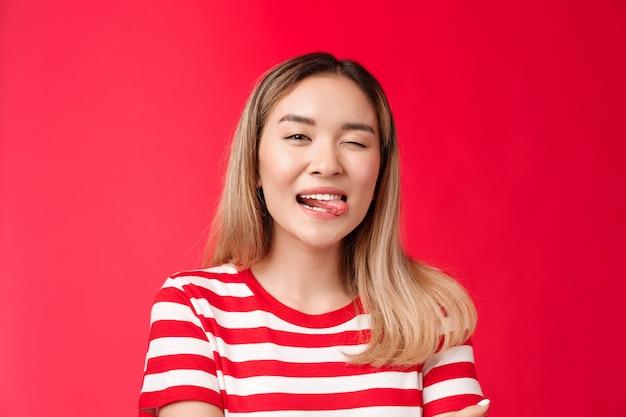 Primo piano sfacciato spensierato in uscita urbano asiatico studentessa godersi le vacanze estive indossare maglietta a righe...