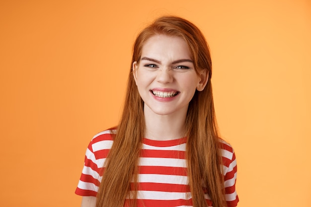 Closeup sassy goodlooking cheerful redhead sly girl smiling toothy white perfect grin satisfied dent...