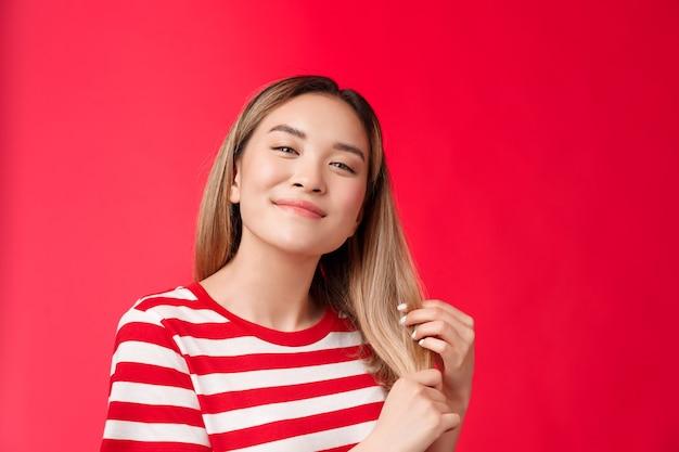 Primo piano soddisfatto ragazza bionda asiatica spensierata carina che si sente felice e compiaciuta dopo il processo di cura dei capelli...
