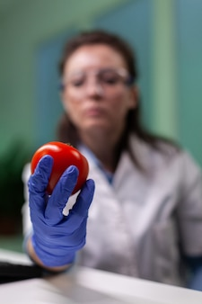 Closeup of scientist reseacher woman analyzing tomato injected with pesticides during scientific agriculture experiment. biochemist scientist doctor working in microbiology hospital laboratory