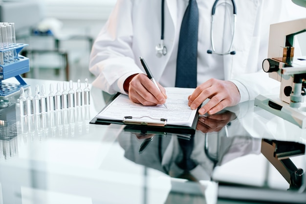 クローズアップの科学者は、研究の結果を健康保護のクリップボードの概念に書き込みます