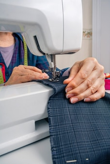 Closeup of seamstress hands working with clothing item on a sewing machine