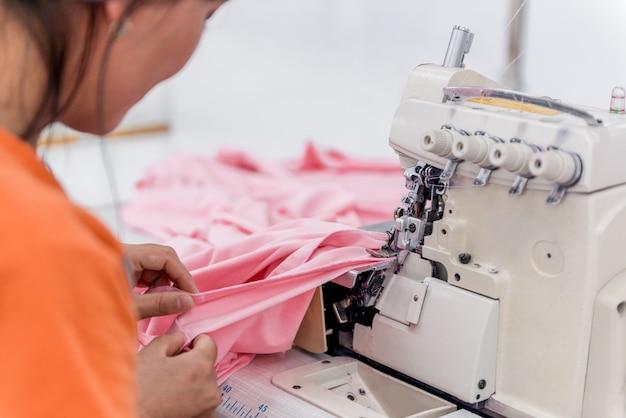 Крупный план швея на машине шьет одежду на швейной фабрике. текстильная мастерская
