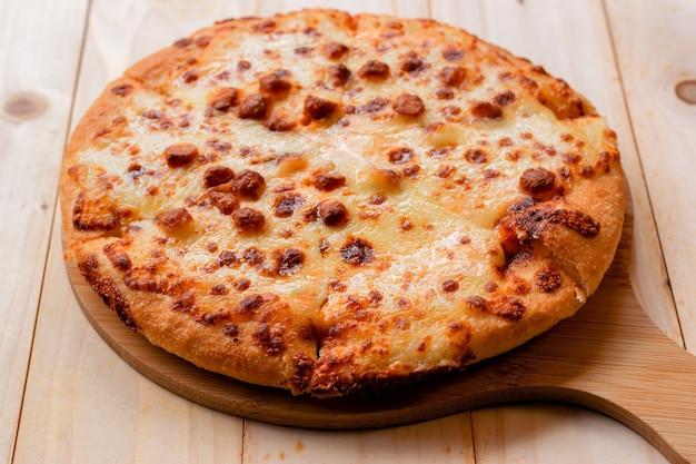 木製のテーブルの上の木製のトレイにピザのクローズアップの選択的な焦点。