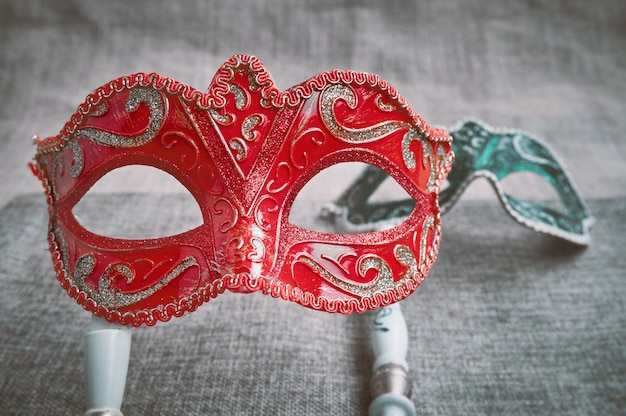 Closeup, selective focus on red venetian masquerade, carnival mask with blurry green mask