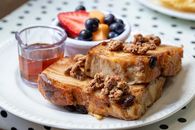 Colpo di messa a fuoco selettiva del primo piano di toast con prugne e frutta, tè sul lato