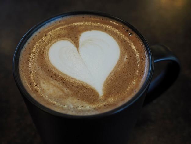 コーヒーカップのハート型ラテアート、テーブルの上のホットラテに焦点を当てたクローズアップ選択的