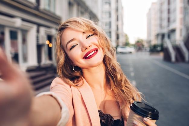 Closeup selfie-portrait pretty blonde girl on street in city. she has vinous lips