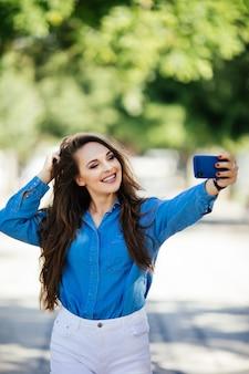 クローズアップselfie-街で長い髪型と真っ白な笑顔のサングラスで魅力的な女の子の肖像画の学生。