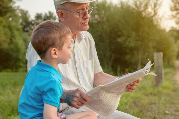 Closeup of senior man and cute child reading a newspaper sitting over a nature background. two different generations concept.