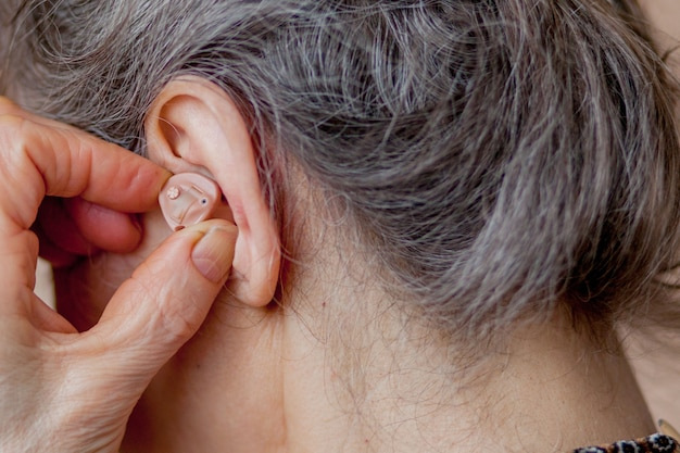 Closeup senior woman inserting hearing aid in her ears