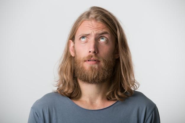 Il primo piano del giovane attraente serio con barba e capelli lunghi biondi indossa la maglietta grigia sembra pensieroso e premuroso isolato sopra il muro bianco
