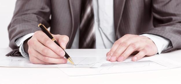 クローズアップ。深刻なビジネスマンがドキュメントに署名し、机の後ろに座っています。白い背景で隔離