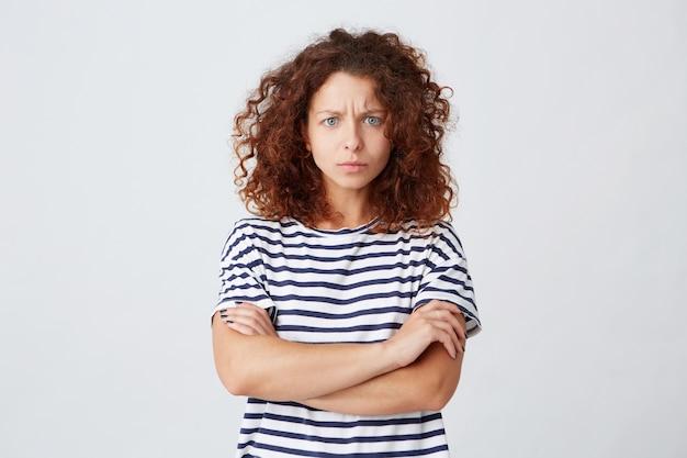 Il primo piano della giovane donna seria preoccupata con capelli ricci indossa la maglietta a strisce si sente imbarazzato