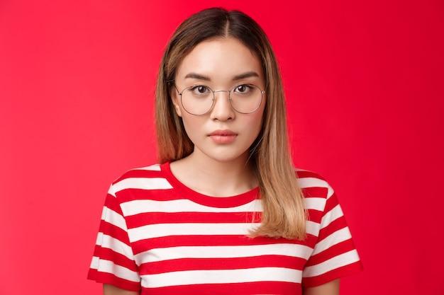 Primo piano serio, concentrato, intelligente, giovane studentessa asiatica, ascolta attentamente la lezione, guarda la telecamera...
