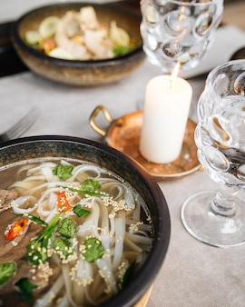 Closeup on served table with pho bo soup in a bowl and glasses of water