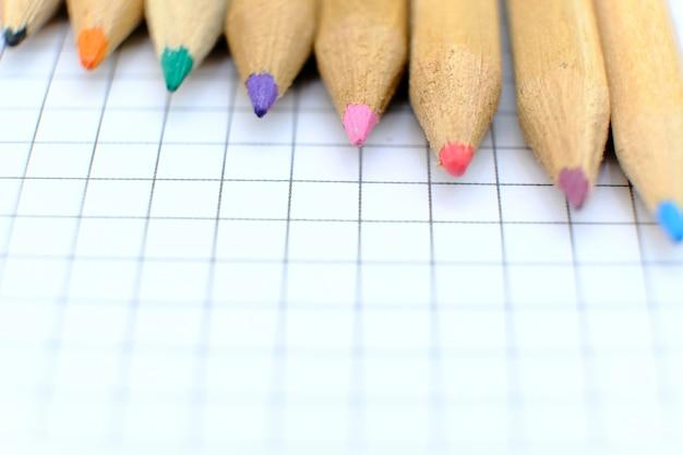 Комплект крупного плана красочных карандашей на checkered бумажном листе тетради для чертежа. обратно в школу концепции.