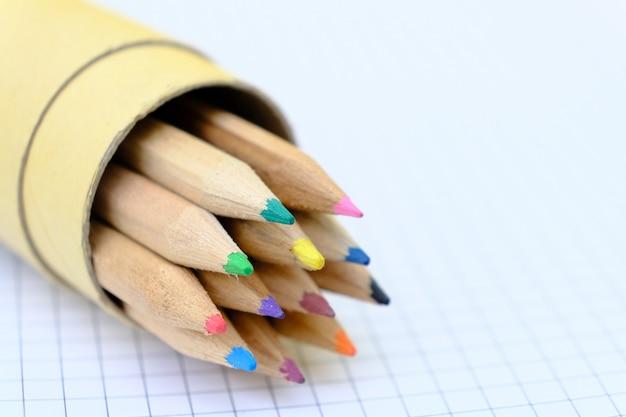 Комплект крупного плана пестротканых карандашей в коробке на checkered бумажном листе тетради для чертежа. обратно в школу концепции.