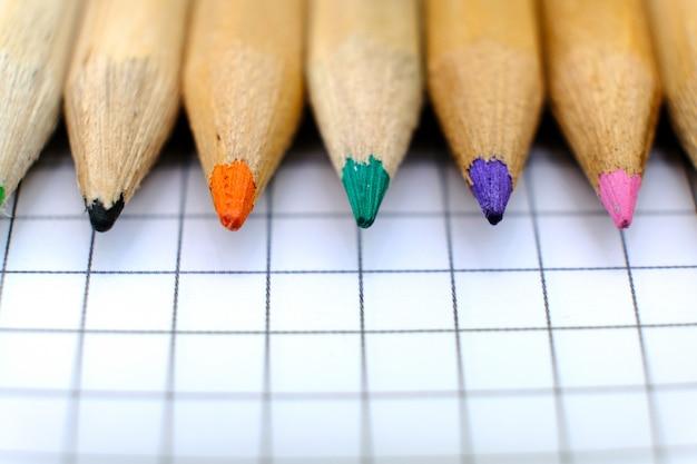 Макрофотография набор разноцветных карандашей на клетчатый лист бумаги тетради для рисования. обратно в школу концепции.