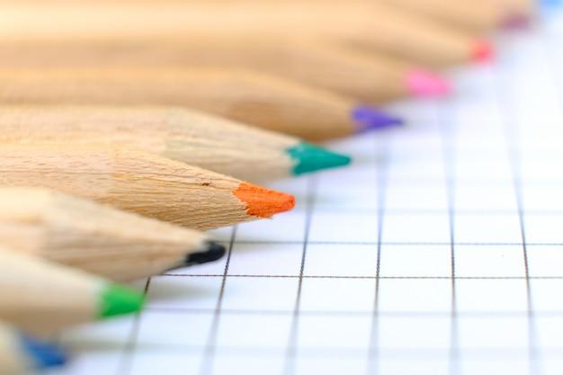 Макрофотография набор разноцветных карандашей на клетчатый лист бумаги тетради для рисования.