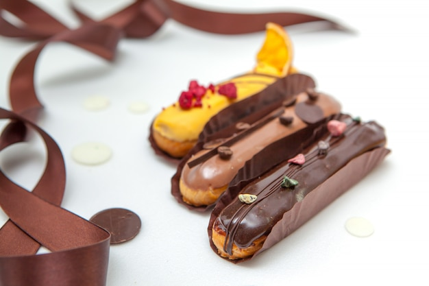 Closeup of set of several eclairs with various fillings and designs, the concept of french cuisine