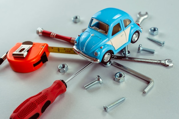 Closeup set of tools wrenches with blue toy car.