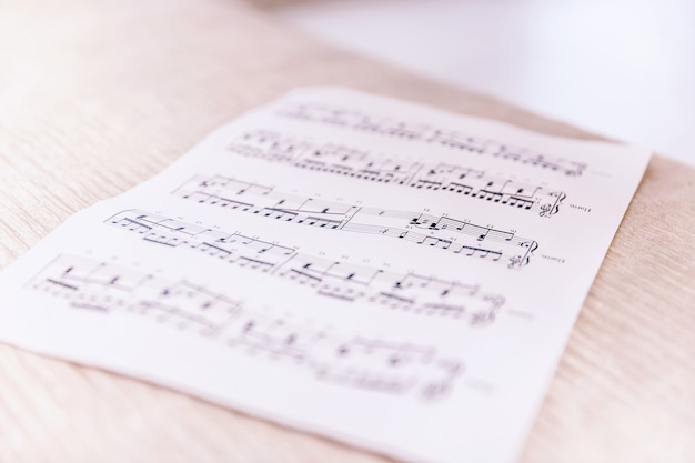 Closeup sheet with musical notes lying on the bed