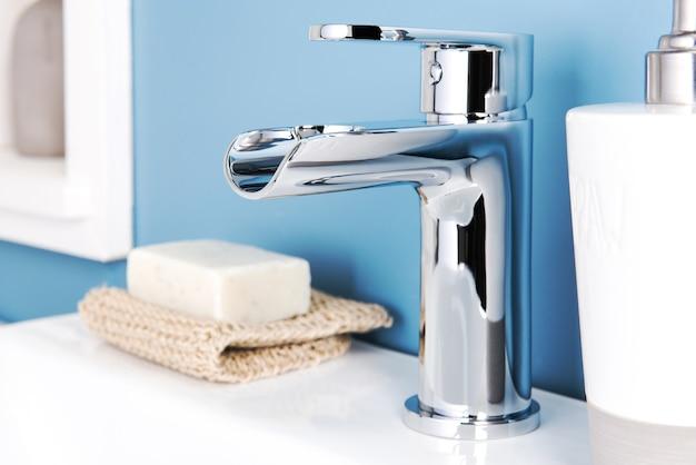 Primo piano di un rubinetto moderno brillante e di un distributore di sapone in un bagno
