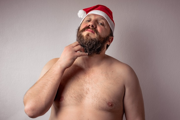 Closeup of a shirtless bearded man wearing a santa claus hat on a grey background