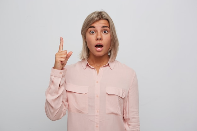 Closeup of shocked astonished blonde young woman with opened mouth wears pink shirt looks amazed and points up with finger isolated over white wall