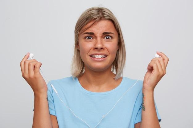 Primo piano della giovane donna bionda confusa scioccata indossa la maglietta blu che tiene gli auricolari, sembra imbarazzata e ascolta musica isolata sopra il muro bianco
