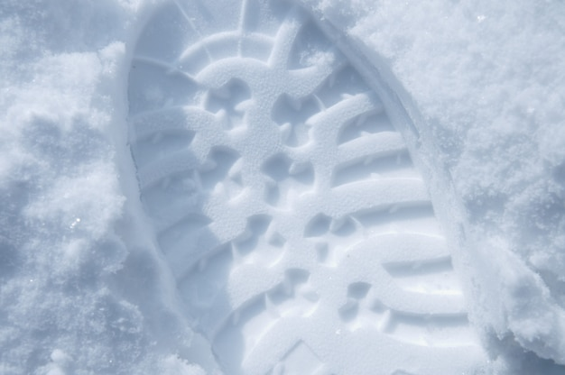 Closeup of shoe print in snow, overhead view
