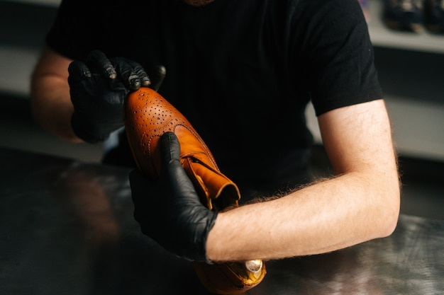 Closeup of shoemaker in black gloves rubbing paint on toe cup of brown leather shoes with fingers