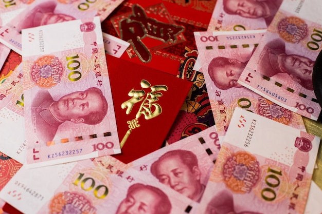 Closeup shot of 100 chinese yuan (cny) banknotes and chinese traditional red envelop