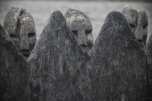 Closeup shot of ancient danish viking figures made with stone behind a wooden fence