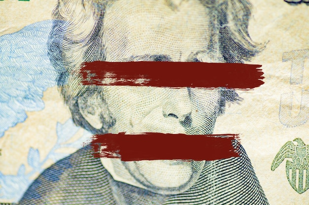 Closeup shot of the andrew jackson face on dollar bill with lines painted over the eyes and mouth
