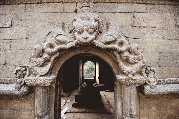 Closeup shot of an arched doorway with sculpting at a hindu temple in nepal